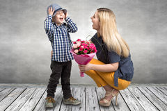 Small son gives his beloved mother a beautiful bouquet of pink roses . Spring, concept of family vacation. Women`s day,mother`s da. Spring, concept of family stock image