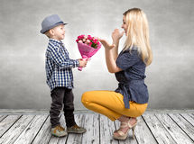 Small son gives his beloved mother a beautiful bouquet of pink roses . Spring, concept of family vacation. Women`s day,mother`s da. Spring, concept of family stock photo
