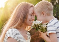 Small son gives his mother a bouquet of delicate flowers. A small son gives his mother a bouquet of delicate flowers. Love, the concept of family recreation stock photo