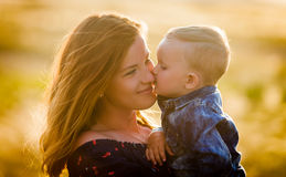 A small son kisses his mother on the field. A small son kisses his mother in the evening field Royalty Free Stock Image