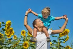 Small son with mum among sunflowers Royalty Free Stock Photos