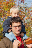 Small son sits on shoulders at the father. Walk in autumn park in solar weather stock image