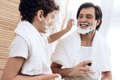 Small son smears father`s face with shaving foam. stock photo