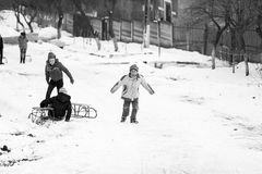 Small southern romanian village. Scenes from a moody winter with children playing with sledges and enjoying the snow Royalty Free Stock Photos