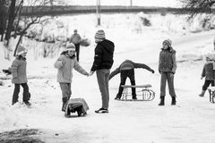 Small southern romanian village. Scenes from a moody winter with children playing with sledges and enjoying the snow Royalty Free Stock Images