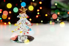 A small souvenir Christmas tree made of glass on the background of twinkling Christmas lights, bokeh effect. royalty free stock photos
