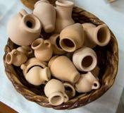 Small souvenir clay pots in a wicker basket Stock Image