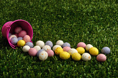 Small speckled easter eggs spilling out of a pink bucket Stock Photography