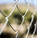 Small spider web on a metal fence stock image