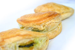 Small spinach pastries. Close-up of three small spinach pies Royalty Free Stock Photos