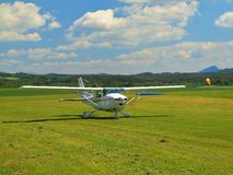 Small sport airplane is rolling or moving on grass airport.Tree edge propeller is quickly turning Royalty Free Stock Photos