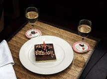 A Small Square Chocolate Birthday Cake With The Inscription Happy And One Candle On