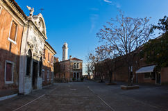 Small square at Murano island in Venice, with lighthouse in background. Italy royalty free stock photos