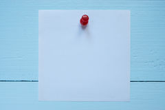 Small square piece of paper pinned to the wall Stock Photo