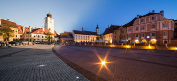 Small Square in Sibiu. Small square with the Old Tower Council in Sibiu, Transylvania, Romania. Day to Night Panorama Royalty Free Stock Images