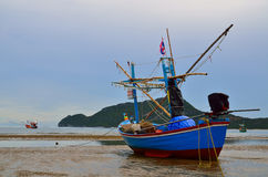 Small squid fishing boat on beach Stock Photo
