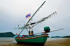 Small squid fishing boat on beach Royalty Free Stock Image