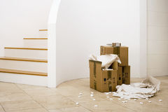 Small stack of boxes, paper and packing foam beside staircase in sparse room Royalty Free Stock Photos