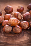 Small stack of hazelnuts on vintage wooden board Stock Photos