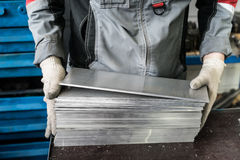 Small stack of steel plates on the bench miller, hand in working. Gloves royalty free stock photography