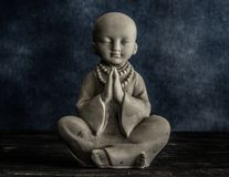 Baby monk praying statuette royalty free stock image