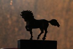 Small statue of horse. A small horse statue is standing in front of beautiful background royalty free stock photo