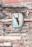 Small statue of Jesus on a cross, Burano, Italy. Small statue of Jesus on the cross, on a brick wall, near 2 statues of angels, Venice, Italy stock photos