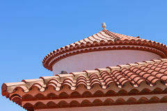 Small statue on the red tiled roof Stock Photo