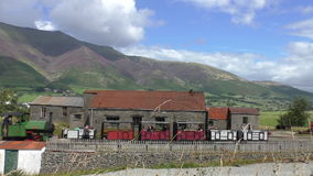 Small steam train in mountain scenery. Vintage steam engine train arrived at small station in Lake District stock video