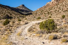 Small steep butte above rough winding dirt road stock images