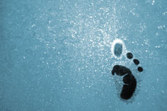 Small step on icy glass. Small humanoid foot step on blue icy window glass stock image