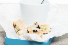 Small stollen cakes in parchment paper in front of a white cup Royalty Free Stock Image