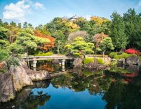 Small stone bridge over the pond at Koko-en Garden in autumn in Himeji, Japan. Small stone bridge over the pond full of koi fish at Koko-en Garden in autumn royalty free stock photos