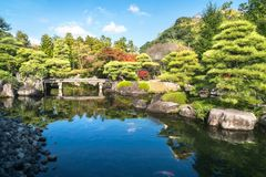 Small stone bridge over the pond at Koko-en Garden in Japan. Small stone bridge over the pond, full of Koi fish, at Koko-en Garden on a beautiful sunny day, with royalty free stock photography