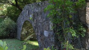 Small stone bridge over a stream stock footage