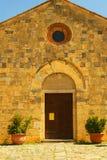 Italian rock church in Tuscany. Small stone church in Tuscany, Italy with plants and heavy plank door royalty free stock image