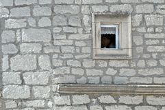 Small, stone framed and lace decorated window on stone built facade. Detail of stone built facade with small, lace decorated and stone framed window in ancient stock images