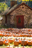 Small stone house in Autumn. A small stone house surrounded by pumpkins in Autumn Royalty Free Stock Photo