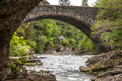 Small stone house in the forest. Small stone house at the river in the forest of Scotland, view under the stone bridge Royalty Free Stock Image
