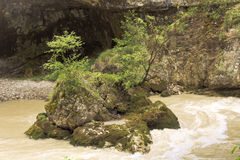 Small stone islet in the rushing water of a mountain stream.Chegem gorge. Royalty Free Stock Photos