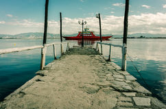 Small stone pier and ferry at Mediterranean lagoon Royalty Free Stock Images