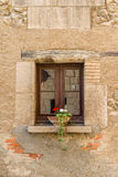 Small stone window with a flower pot Royalty Free Stock Photos