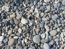 SMALL STONES. ON THE BEACH, SHADES OF GREY, SUNNY DAY Royalty Free Stock Image
