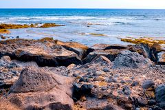 Small stones on a black beach, in the background are akean waves and a surfer royalty free stock photos