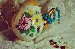 Small stones. Glassware,saucer,beads,,white cloth,flower,dishes,dinner set,gold kettle with turquoise,decoration Royalty Free Stock Images