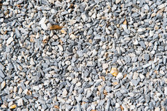 Small stones or gravels. Natural texture outdoors on sunny day on grey pebble background Royalty Free Stock Images