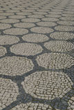 Small stones are often used in Portugal to make geometric patterns on sidewalks Royalty Free Stock Images
