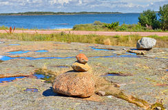 Small stones pyramid on rocky shore of Baltic Sea Royalty Free Stock Photo