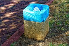 Small stones trash can with a blue garbage bag Royalty Free Stock Photo