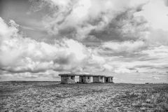 Small stony empty houses on grass and cloudy sky Stock Images